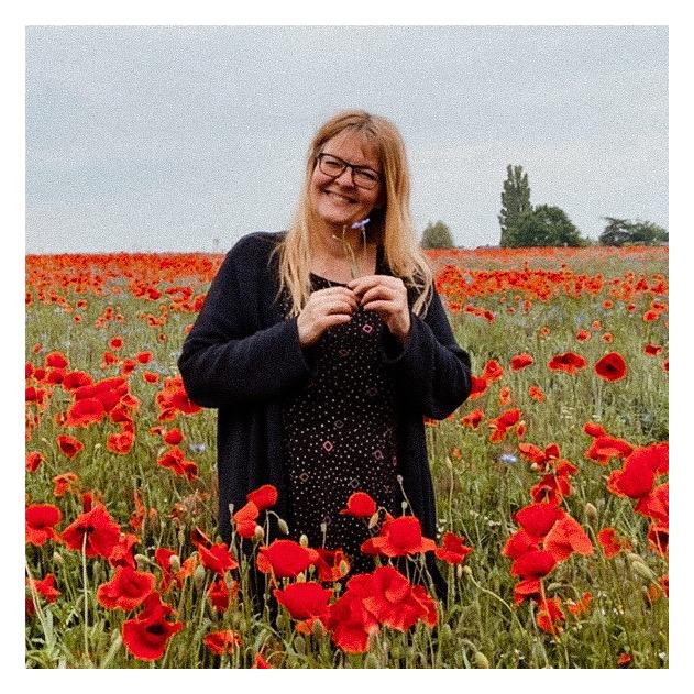 Die Berliner Autorin Petra A. Bauer mitten in einem Mohnfeld.